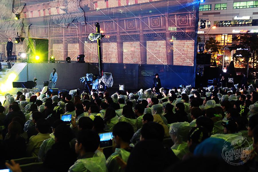 우비를 입고 공연을 관람하는 관객들